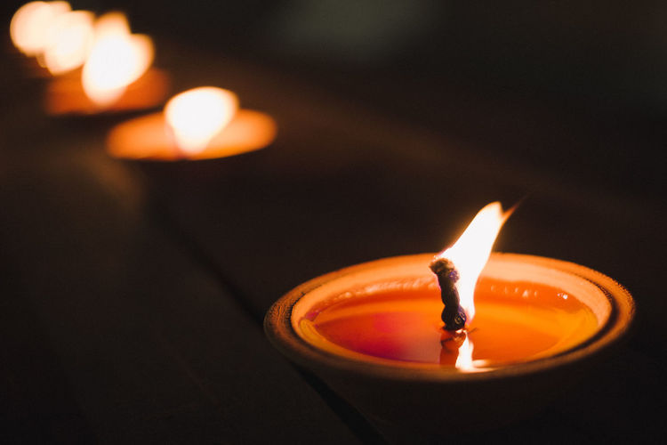 Burning Candle Close-up Dark Domestic Room Electric Lamp Event Fire Fire - Natural Phenomenon Flame Focus On Foreground Glowing Heat - Temperature Illuminated Indoors  Light - Natural Phenomenon Lighting Equipment Luminosity Melting Nature No People Oil Lamp Orange Color Tea Light