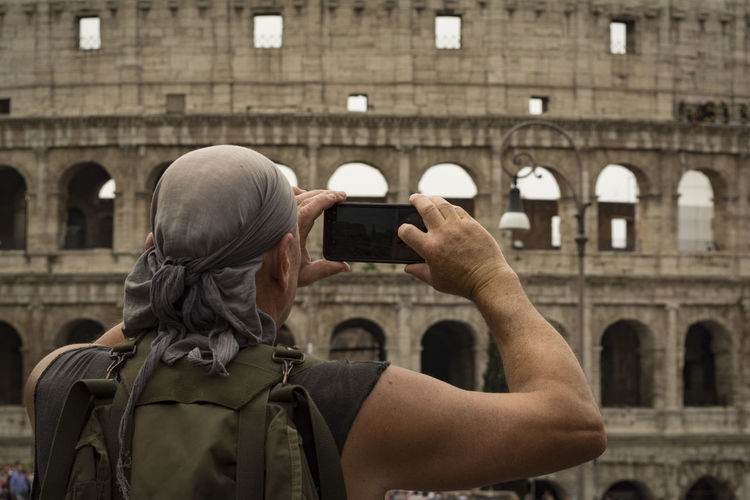 Rear view of man photographing amphitheater with mobile phone