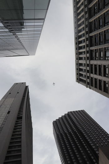 Low angle view of modern buildings against sky with airplane in the center. in chicago