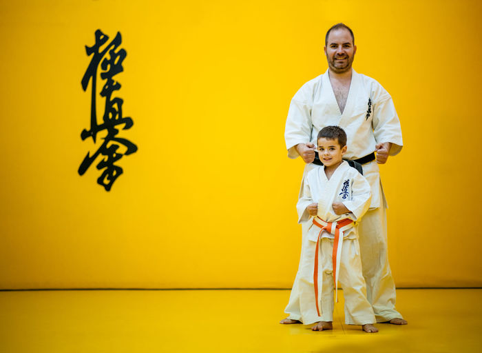 Karate sensei and his student standing in rest position in karate dojo. Men Males  Smiling Two People Adult Togetherness Childhood Happiness Standing Indoors  Full Length Non-western Script Emotion Portrait Looking At Camera People Mature Men Positive Emotion