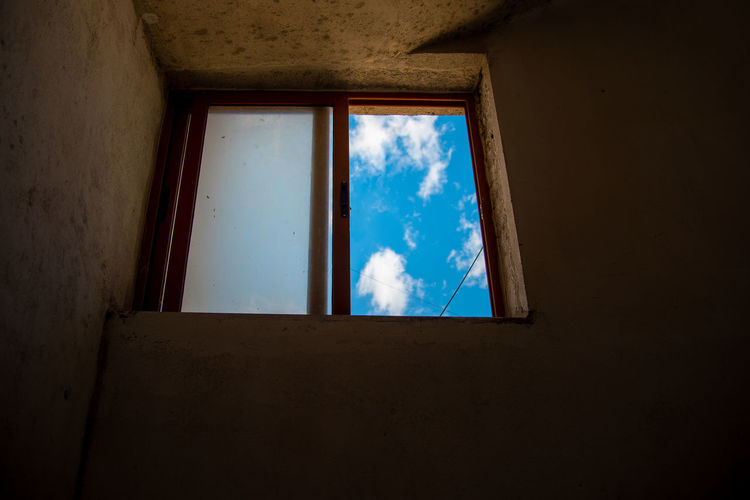 Low angle view of window in abandoned building