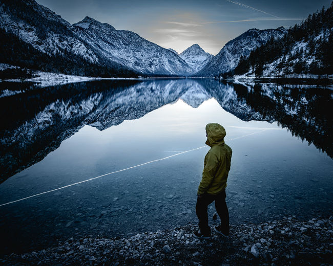 Man standing by lake against snow mountains during winter