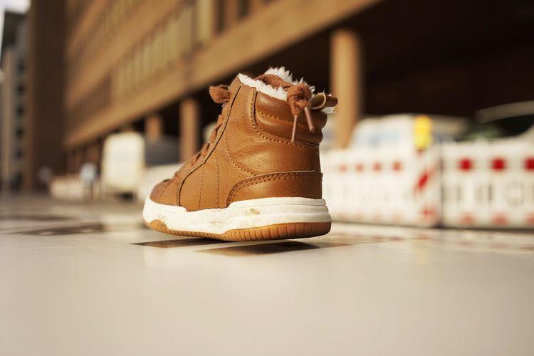 Brown Shoe In Mid-Air
