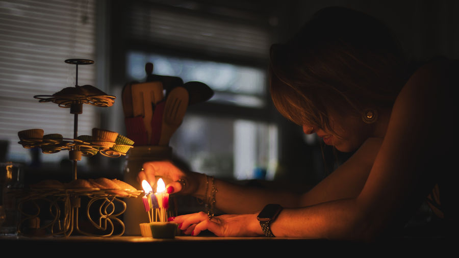 Woman holding burning candles on table