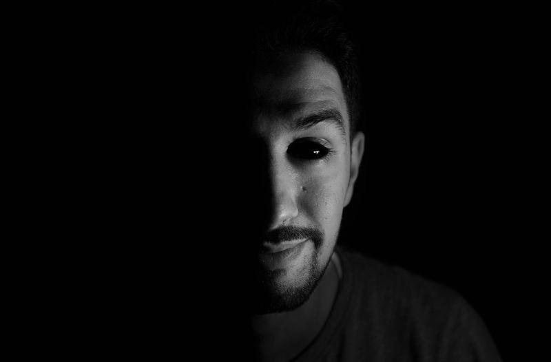 Close-Up Portrait Of Mid Adult Man Against Black Background