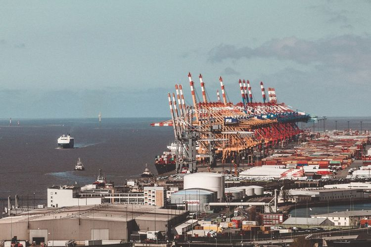 High angle view of commercial dock by sea against sky