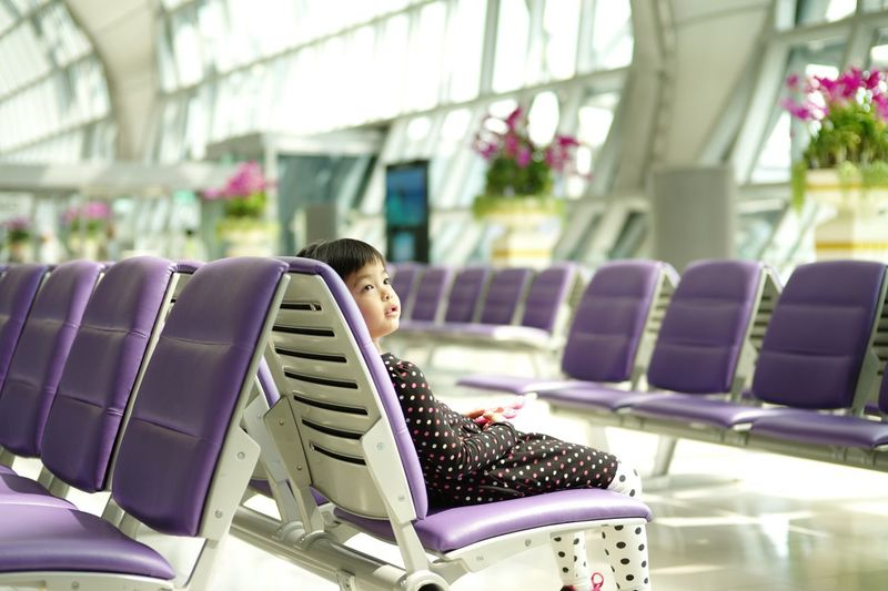 Cute girl sitting on chair at airport