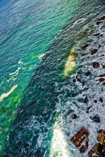 High angle view of waves splashing on sea