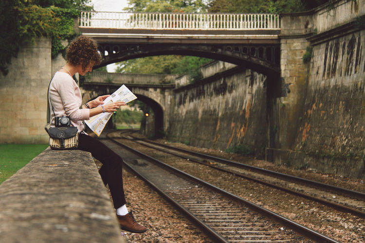 Woman sitting on retaining wall reading newspaper by railroad tracks