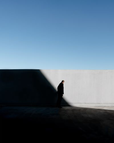 Side view of man standing by concrete wall during sunny day