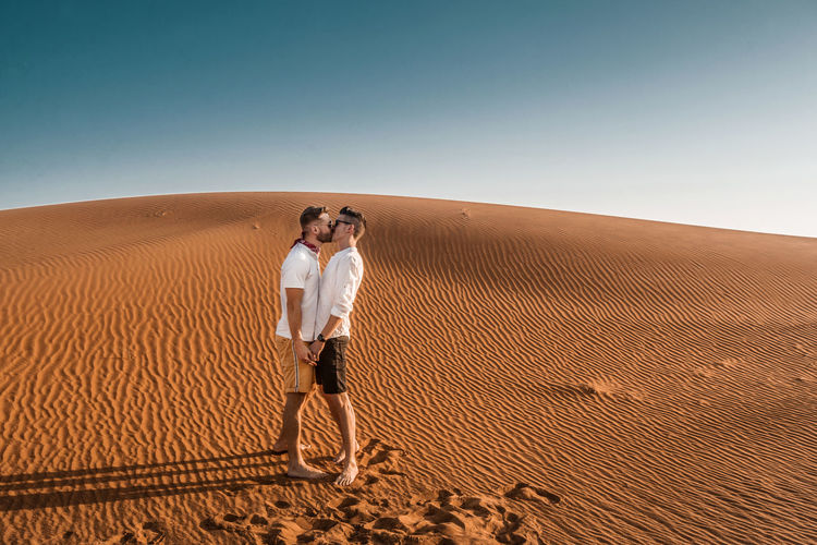Desert Sand Dune Sand Sky Land Landscape Adult Full Length Clear Sky Nature Remote Standing Outdoors Lifestyles Men Gay Gaymen Kiss Reallove Dubai Casual Clothing Leisure Activity Climate Arid Climate Couple