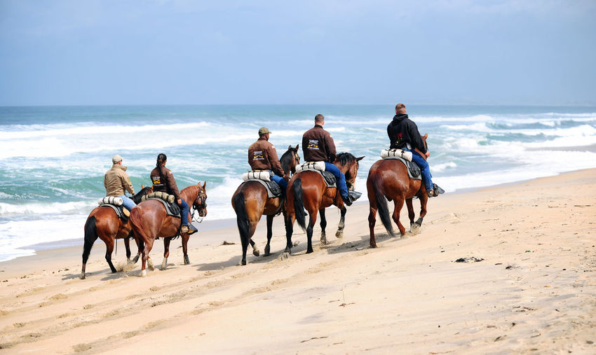 Adult Adults Only Beach Cowboy Cowboy Hat Day Desert Domestic Animals Full Length Horizon Over Water Horse Horse Racing Horseback Riding Mammal Medium Group Of People Men Only Men Outdoors People Riding Running Sand Sea Sky Wild West