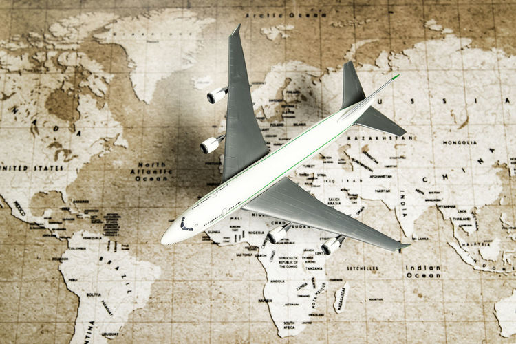one air plane fly over brown map Business Trip Country Passport Tickets Tourist Travel Travelling Trip Air Plane Brown Business Class Close-up Continent Day Economy Class Europe Indoors  No People Paper Tourism Weapon World Map