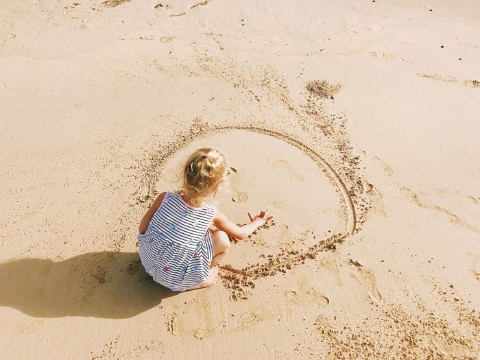 High angle view of girl playing on sand at beach