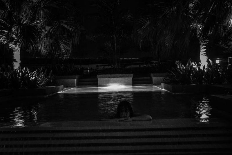 Woman swimming in pool at night