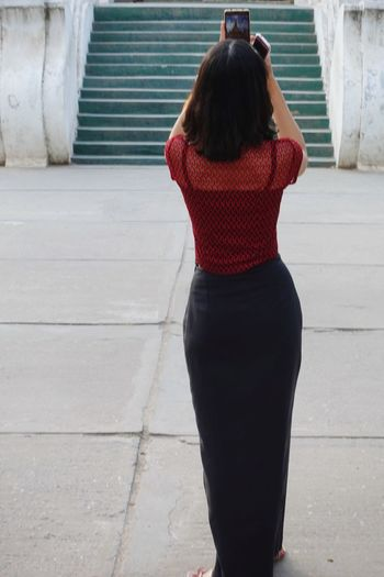 Rear view of woman photographing staircase while standing in city