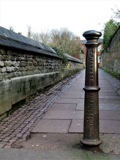 Old bollard in the alley Alley Architecture Bollard Cobblestone Day Iron - Metal Lettering No People Outdoors Stone Material Wall Words