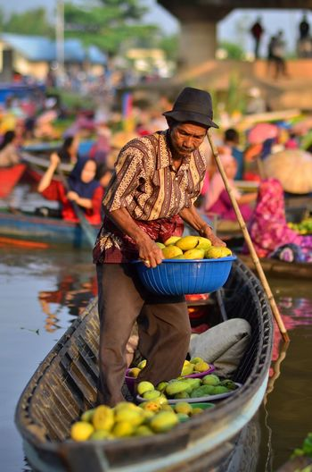 Full length of man holding fruits standing on rowboat