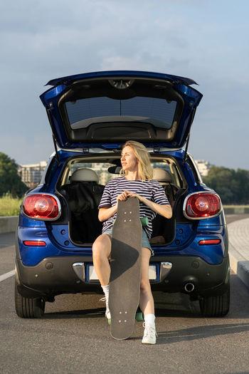 Full length portrait of woman in car