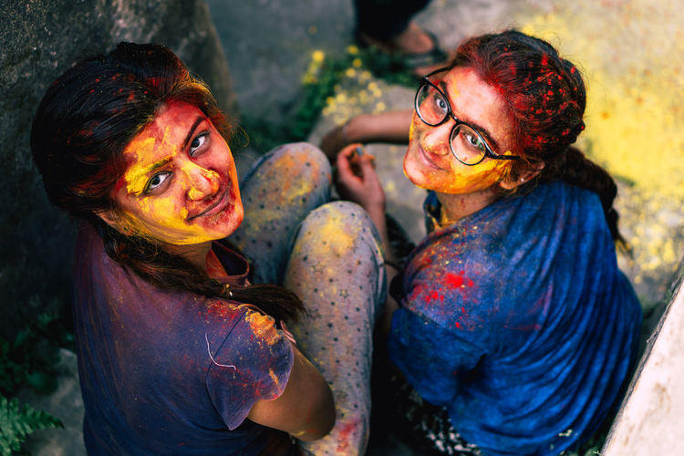 Portrait of smiling friends covered with powder paint sitting outdoors