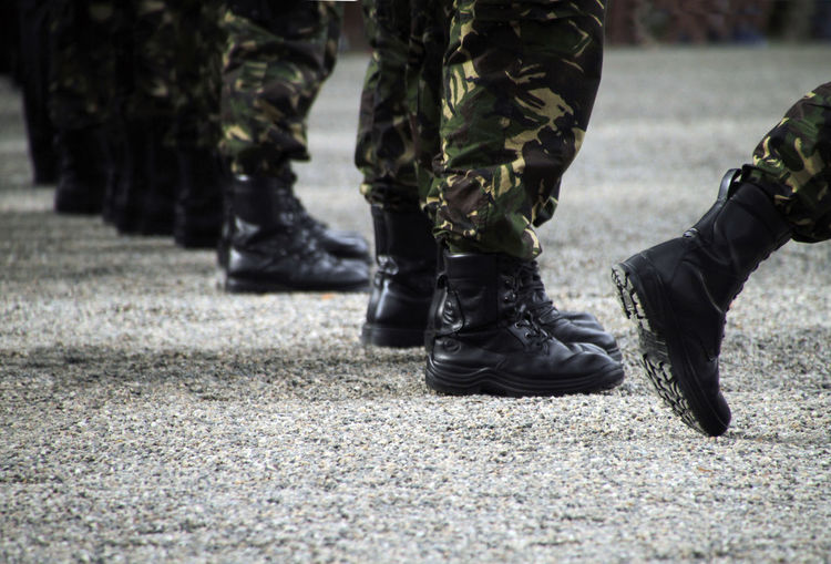 Soliders at a military parade in boots and camouflage clothing