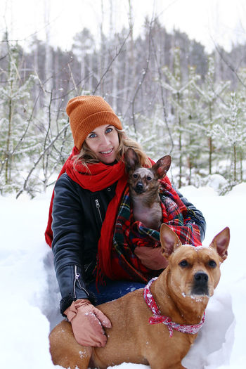 Beautiful smiling woman is on a walk with her two dogs in winter coniferous forest.