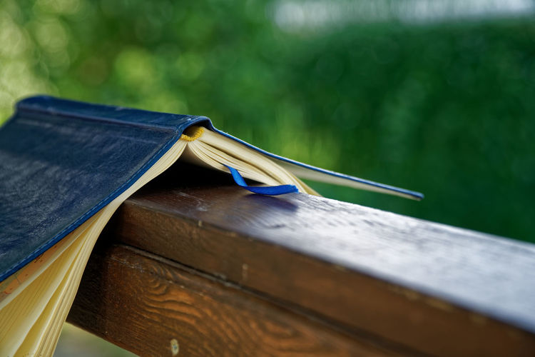 Close-up of upside down diary on railing at park
