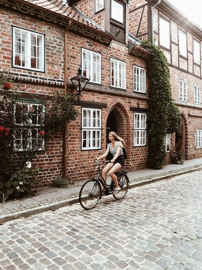 Full Length Of Woman Riding Bicycle On Street Against Building