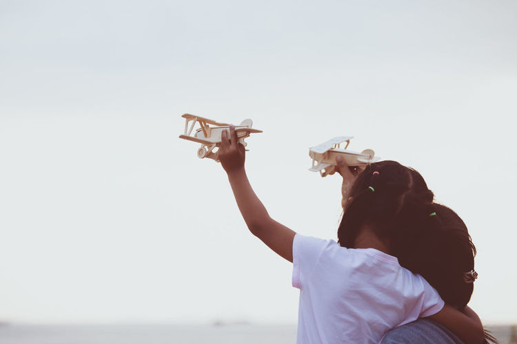 Mother And Daughter Flying Toy Airplane Against Clear Sky