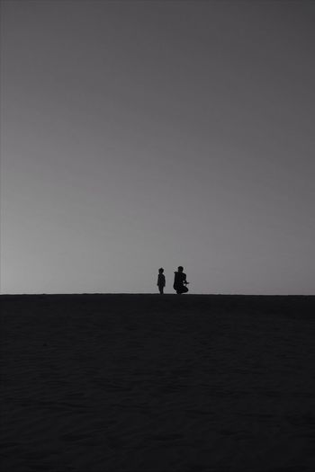 Silhouette Father With Son At Beach Against Clear Sky During Sunset