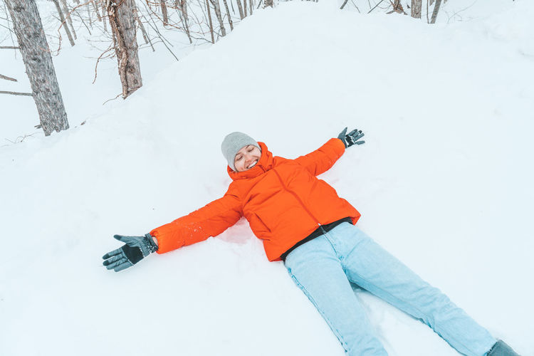 High angle view of woman lying on snow covered field