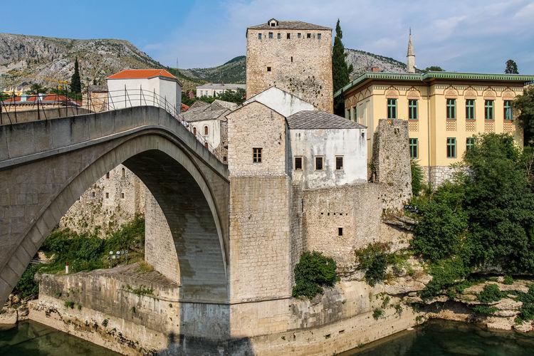 Arch bridge amidst buildings against sky in city