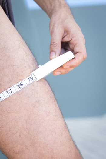 Close-up of man holding tape measure on leg