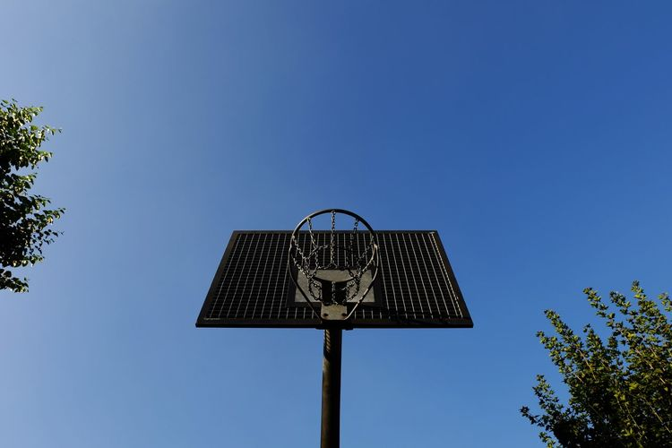 Directly below shot of basketball hoop against clear blue sky on sunny day