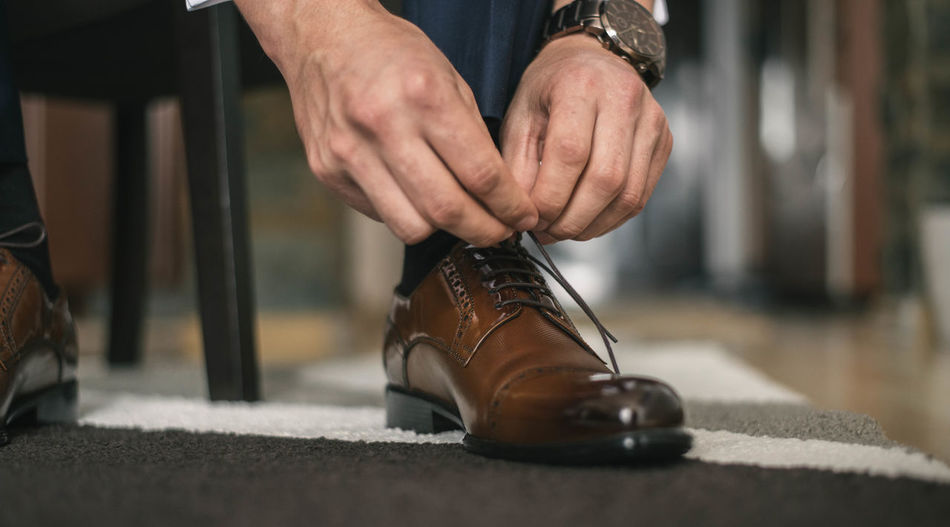 Low section of man tying shoelace at home