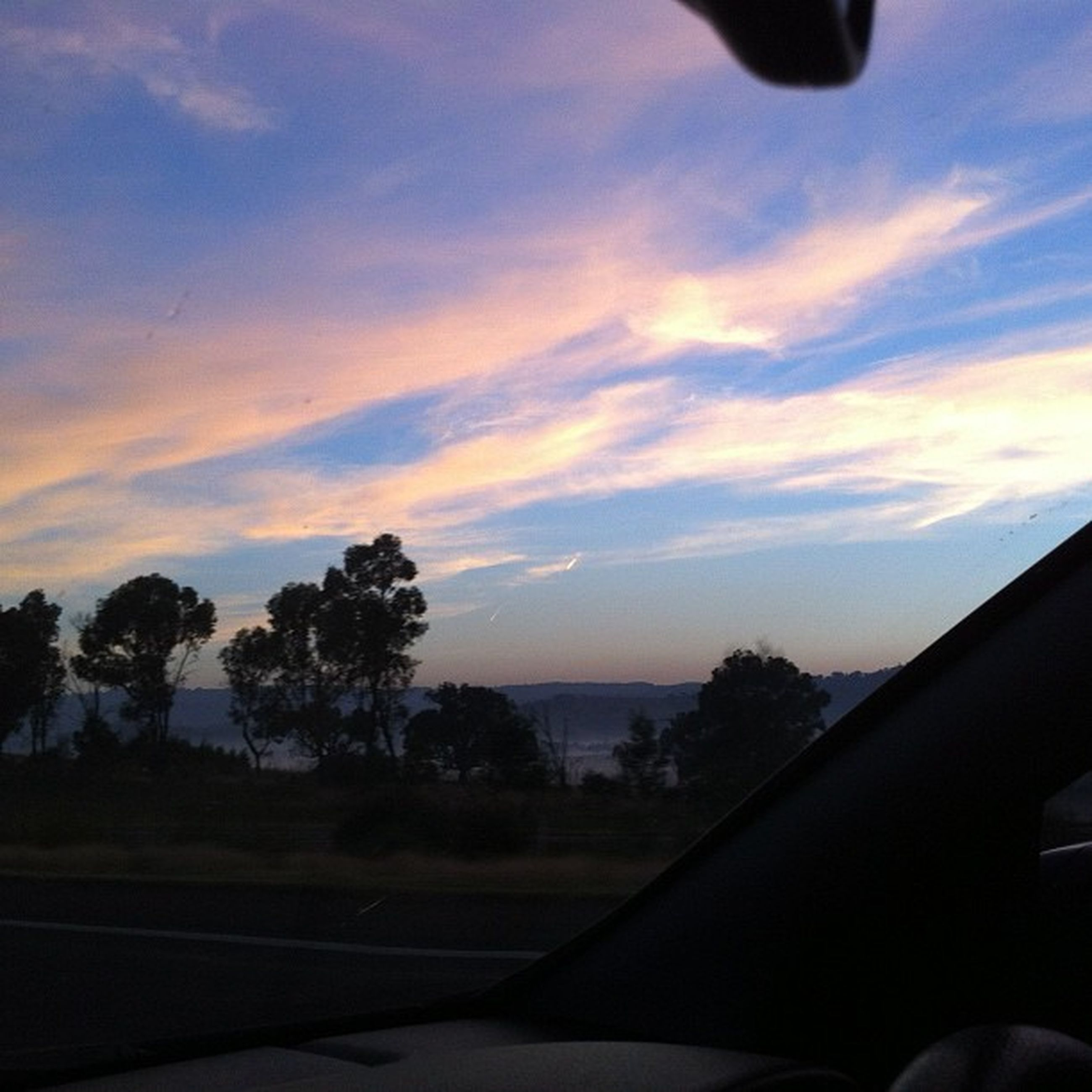 transportation, sky, sunset, cloud - sky, tree, mode of transport, silhouette, scenics, beauty in nature, road, cloud, vehicle interior, part of, landscape, nature, tranquil scene, tranquility, cropped, airplane, car