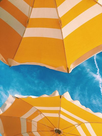 Low angle view of yellow parasols against sky