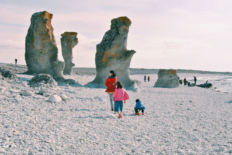 Tourists on rock formation at seaside