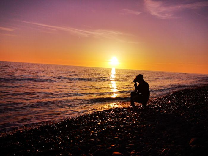 A friend of mine using their camera at sunset Water Sea Full Length Sunset Wave Beach Sitting Silhouette Sun Side View
