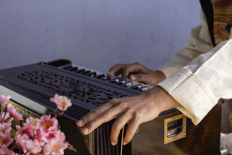 Selective focus on human hand playing harmonium - indian classical instruments