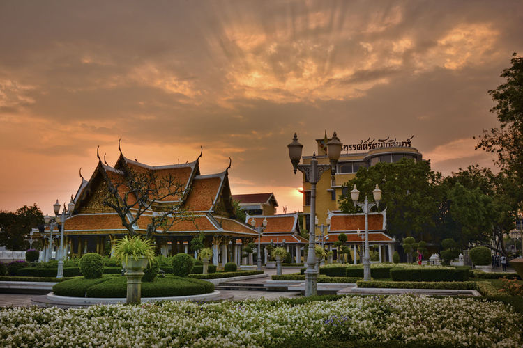 tropical swimming pool at night and Buddhist Temple in thailand Architecture Sky Built Structure Sunset Building Exterior Building Cloud - Sky Plant No People Nature Belief Spirituality Religion Place Of Worship Tree Orange Color Outdoors The Past History