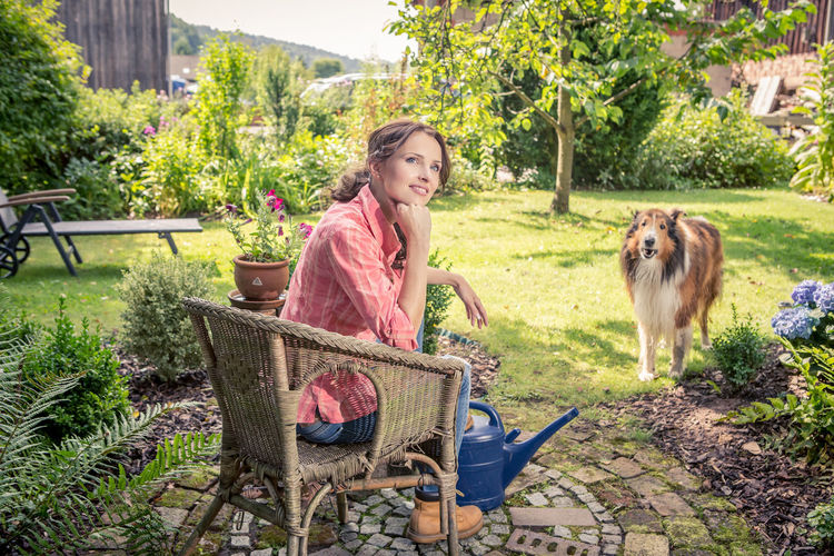 Thoughtful Woman Sitting On Chair In Yard