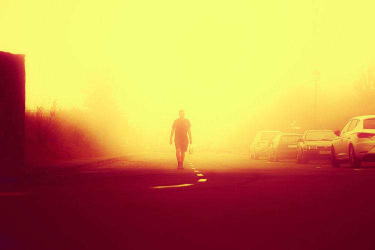 Silhouette man walking on road against sky during sunset