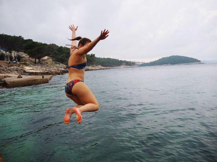 Full length of young woman wearing bikini diving in sea against sky