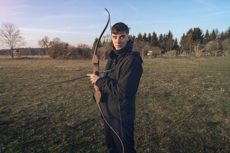 Yong Man Teenager Caucasian Handsome One Person Real People Lifestyles Land Field Plant Holding Nature Leisure Activity Tree Weapon Grass Three Quarter Length Hunter Standing Day Men Looking At Camera Casual Clothing Arrow - Bow And Arrow Outdoors Aggression  Bow Sport Arrow Landscape Rural Scene