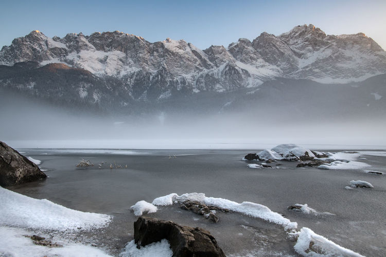 Scenic View Of Frozen Lake By Mountains Against Sky