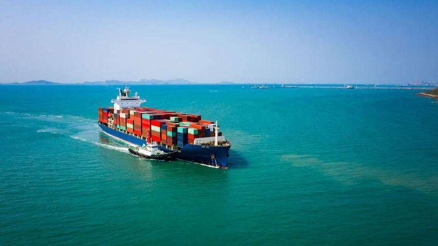 Container ship sailing in green sea and tugboat drag and blue sky background from drone shot