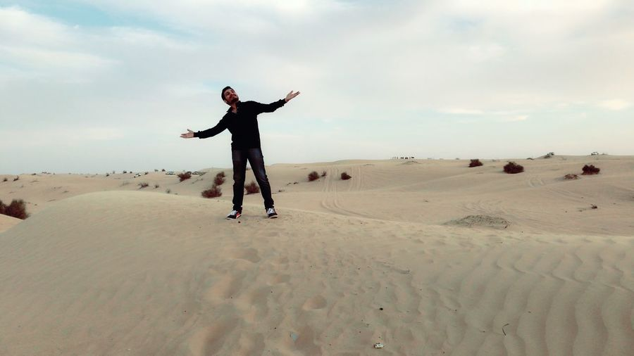 Man With Arms Outstretched Standing At Desert Against Cloudy Sky
