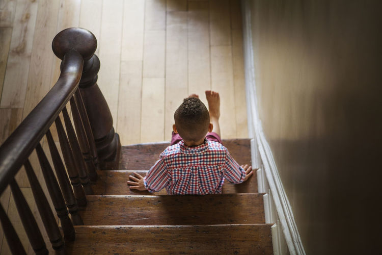Rear view of boy sitting on staircase