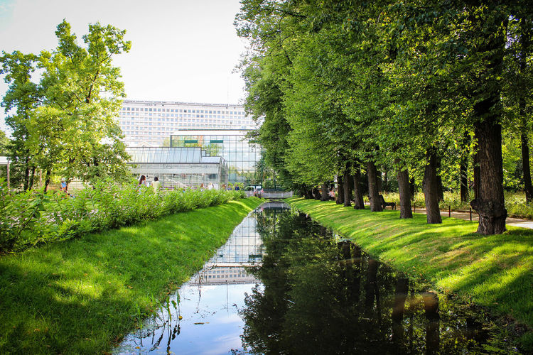 Architecture Beauty In Nature Building Exterior Built Structure City Day Grass Green Color Growth Nature No People Outdoors Puddle Reflection Sky Tree Water